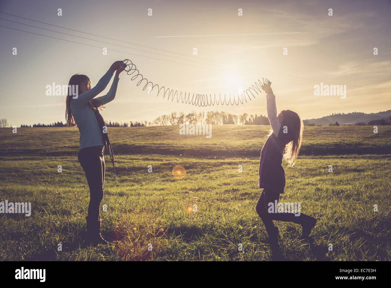 Two little girls playing with a spiral on a meadow in backlight - Stock Image