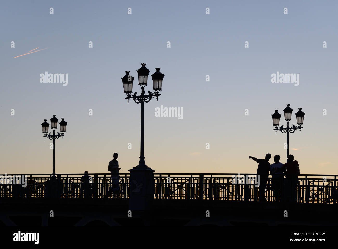 Evening Silhouettes of Street Lamps & People on the Pont St Pierre Bridge over the Garonne River Toulouse Haute - Stock Image