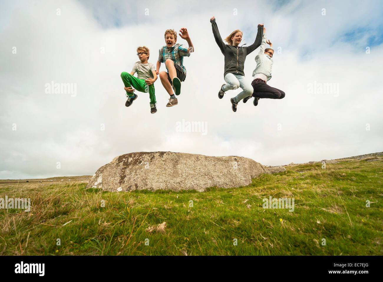 United Kingdom, England, Cornwall, Children jumping from stone - Stock Image