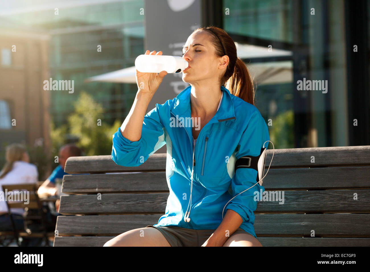 Athletic brunette woman drinking from bottle - Stock Image