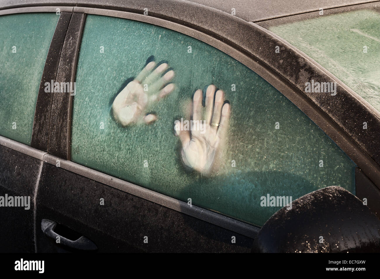 hand print like foot prints melted frost on window to car idea of trapped inside surviving cold spell call for help - Stock Image
