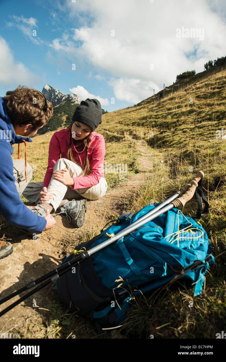 Austria, Tyrol, Tannheimer Tal, young man caring for injured woman on hiking tour - Stock Image