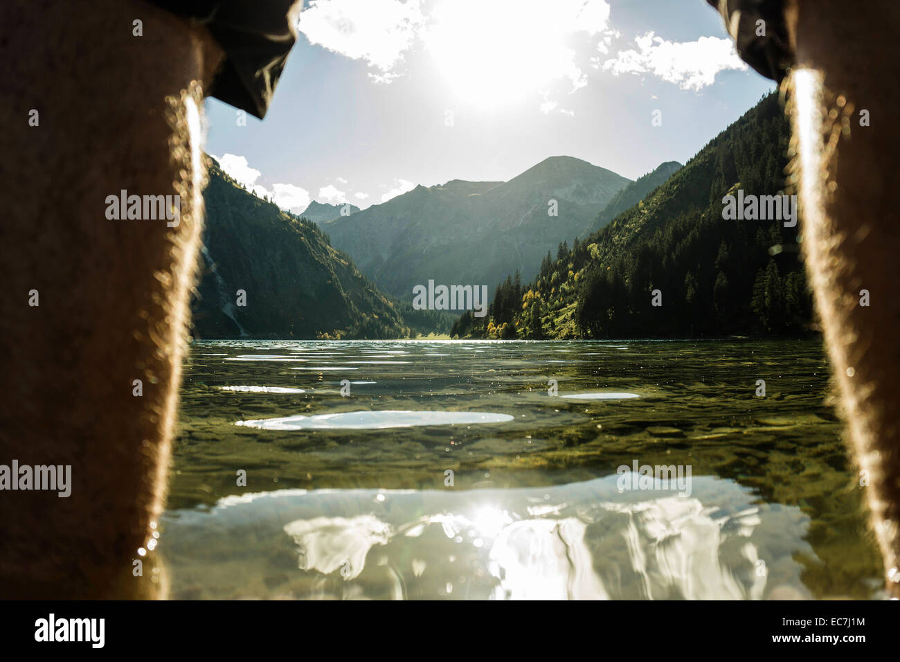 Austria, Tyrol, Tannheimer Tal, legs of a man at lakeshore - Stock Image