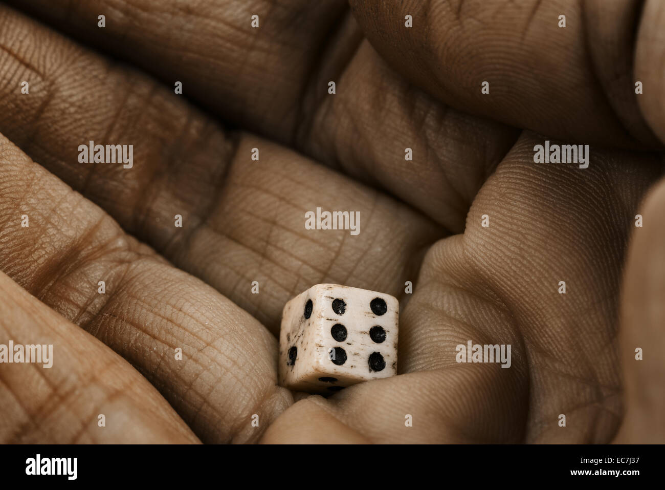 An old Victorian bone dice held in the palm of a hand ready to be thrown and the fate of the throw of the die found - Stock Image