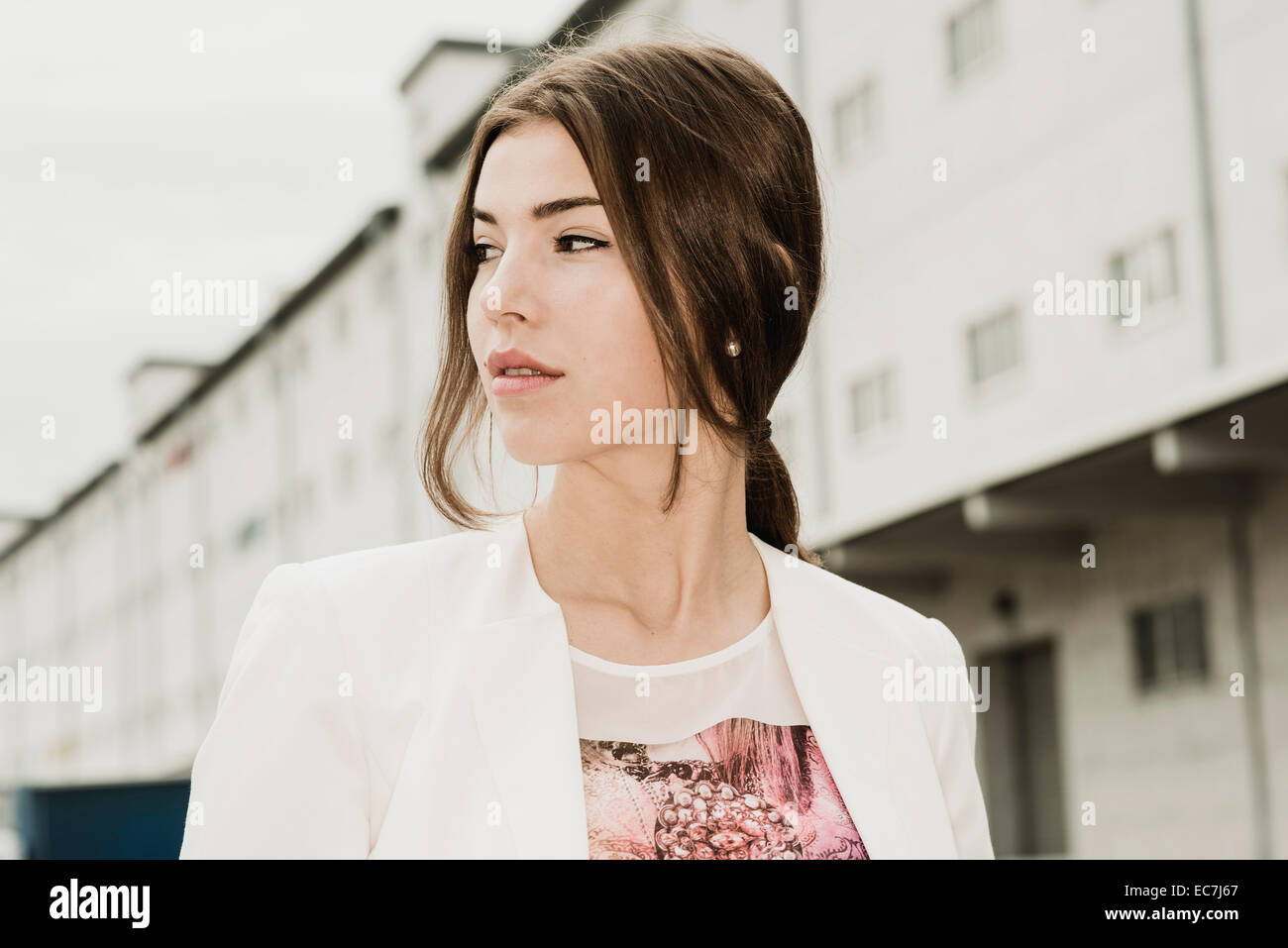 Portrait of young businesswoman watching something - Stock Image