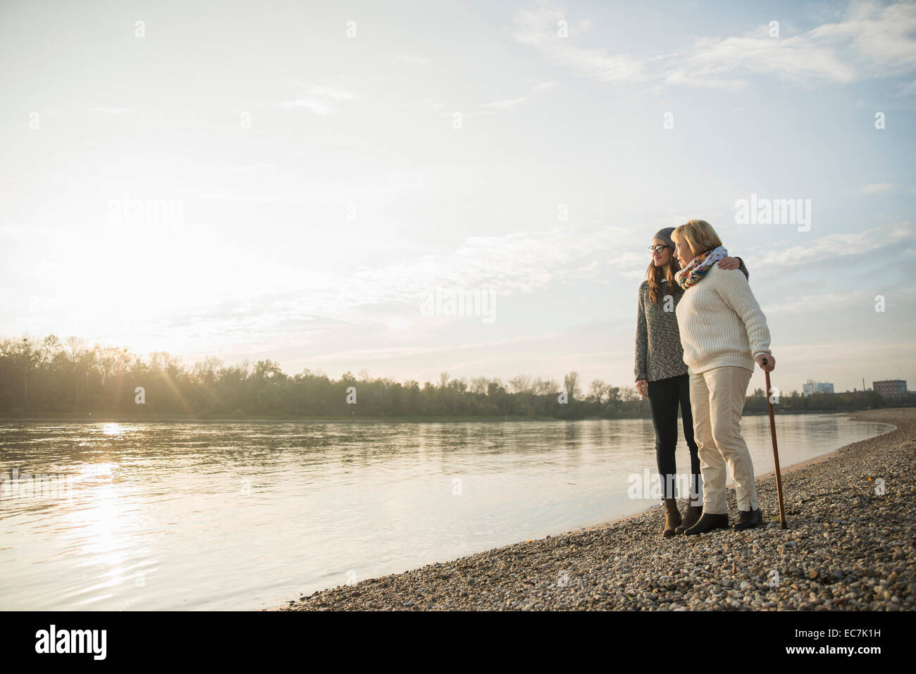 Young woman and her grandmother standing together at water watching sunset - Stock Image