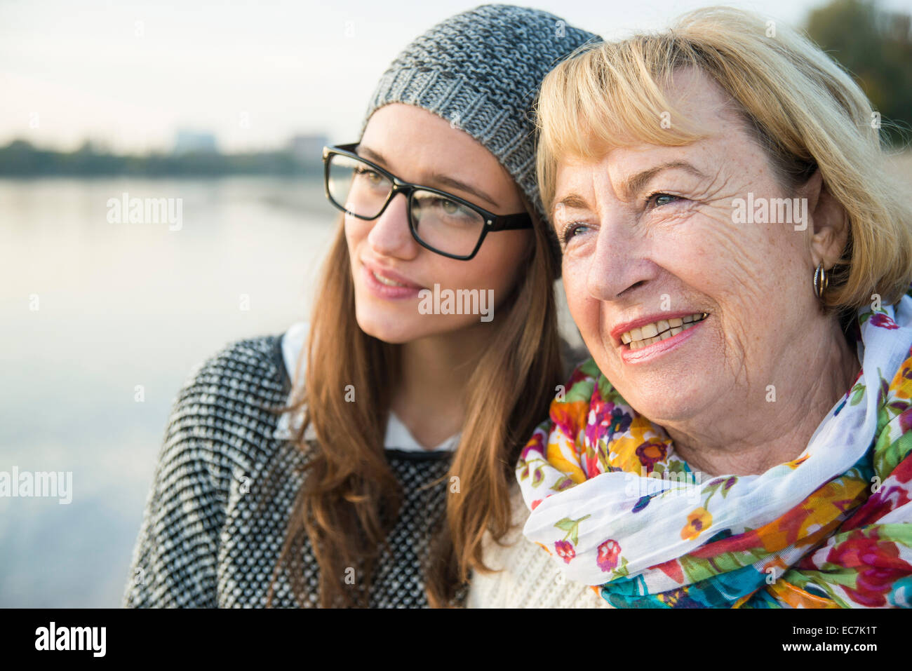 Portrait of senior woman head to head with her adult granddaughter - Stock Image