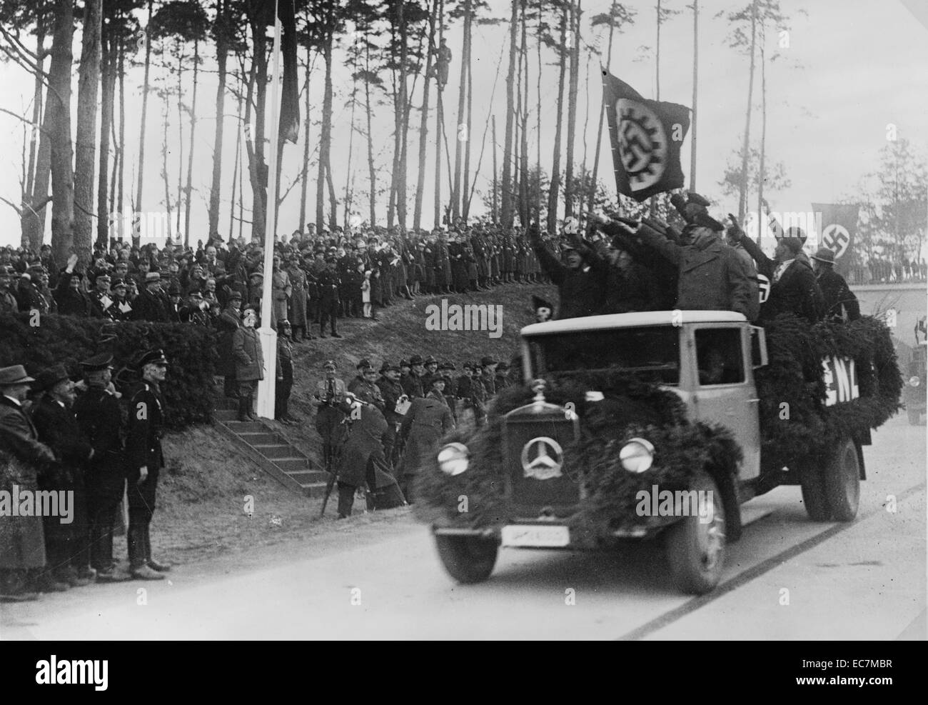 Men standing in the back of a truck salute Hermann Goring and other officials during the inaugural ceremonies for - Stock Image