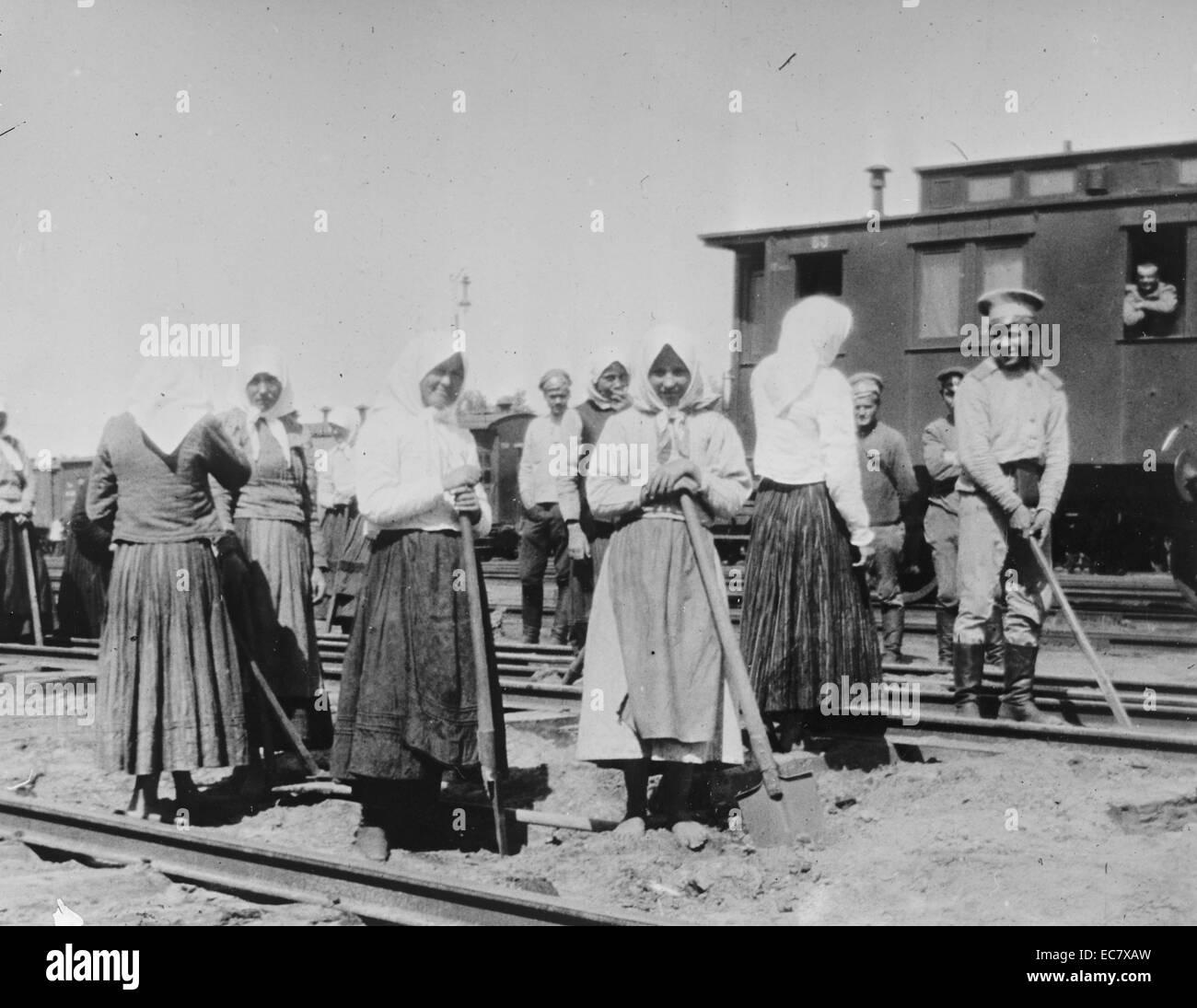 Russian women work on railway tracks as troop train stands nearby; World war One, - Stock Image