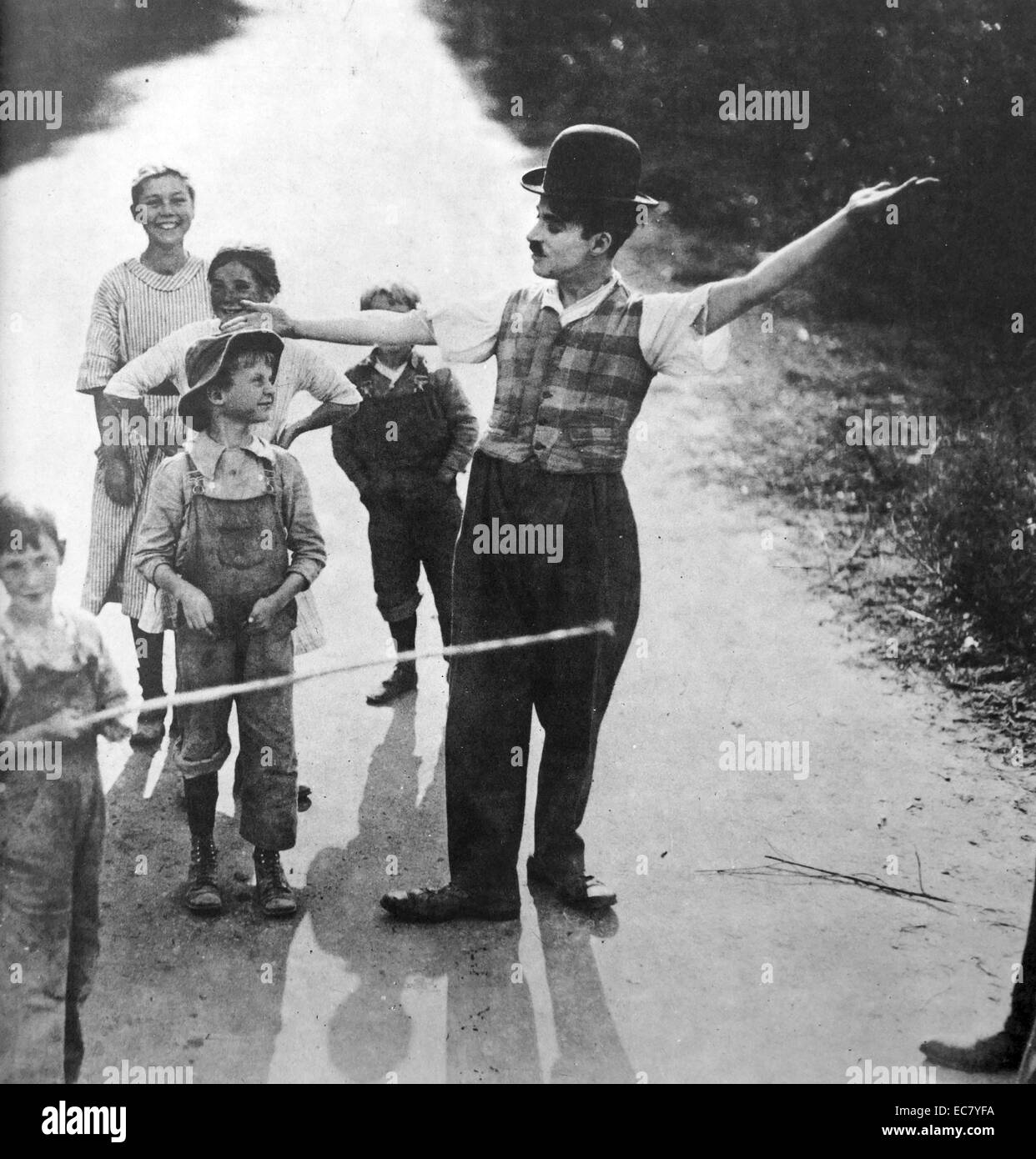 Charlie Chaplin with a group of  children. - Stock Image