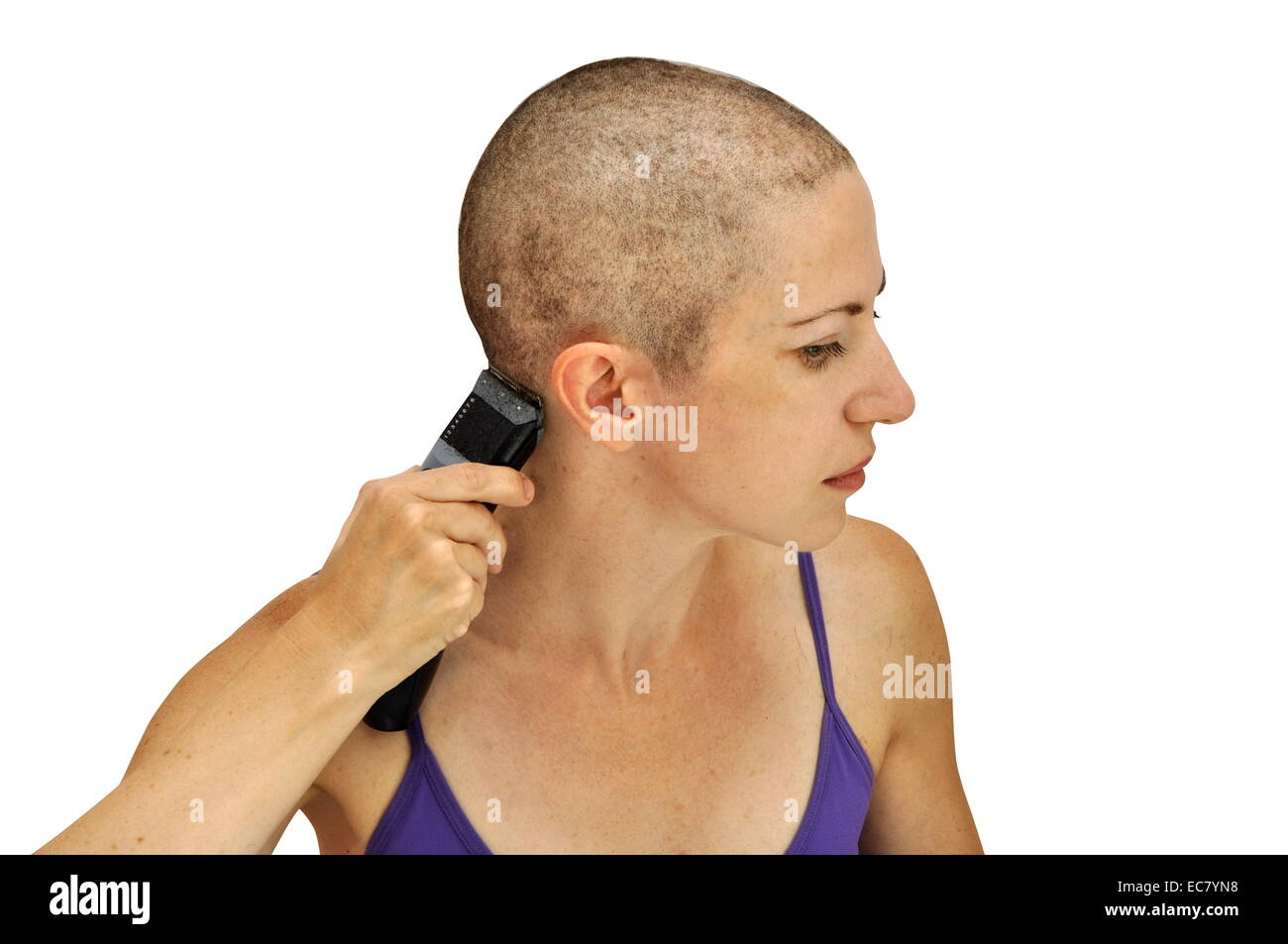 Woman in purple bodice shaving herself bald with clipper, isolated on white. Horizontal composition. - Stock Image