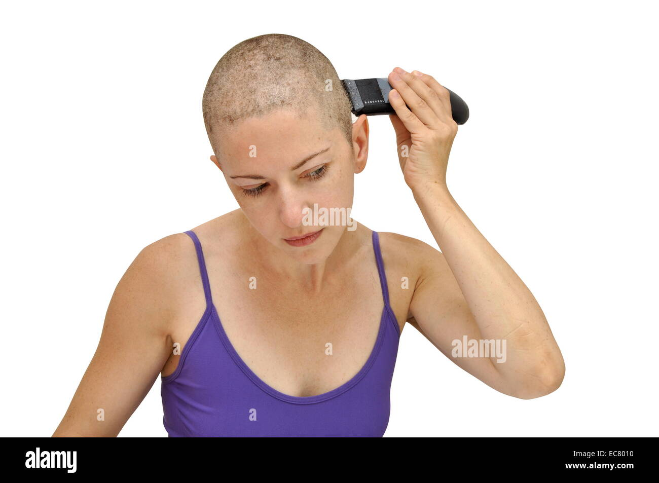 Woman in purple bodice shaving herself bald using left hand, isolated on white. - Stock Image
