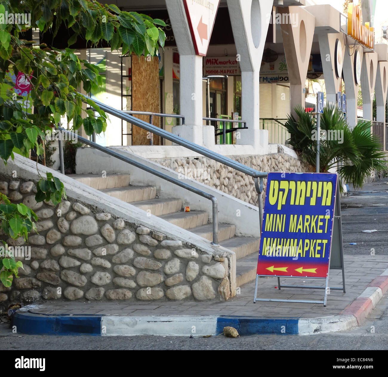 Hebrew; English and Russian sign at a parade of shops in the Ein Bokek hotel and resort village on the Israeli shore - Stock Image