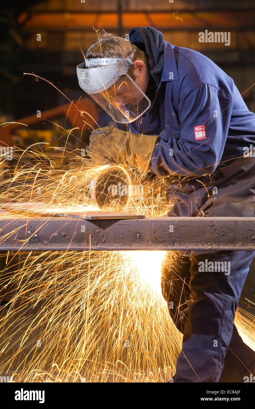 A craftsman wearing personal safety equipment while working with steel and hand tools in an industrial workshop Stock Photo