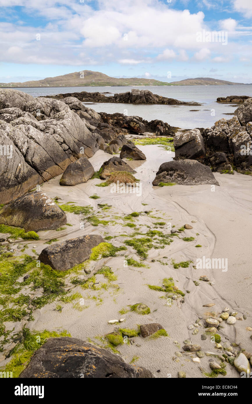 Rocky seashore at low tide with view to Eriskay from Kilbride, South Uist, Outer Hebrides, Western Isles, Scotland, - Stock Image