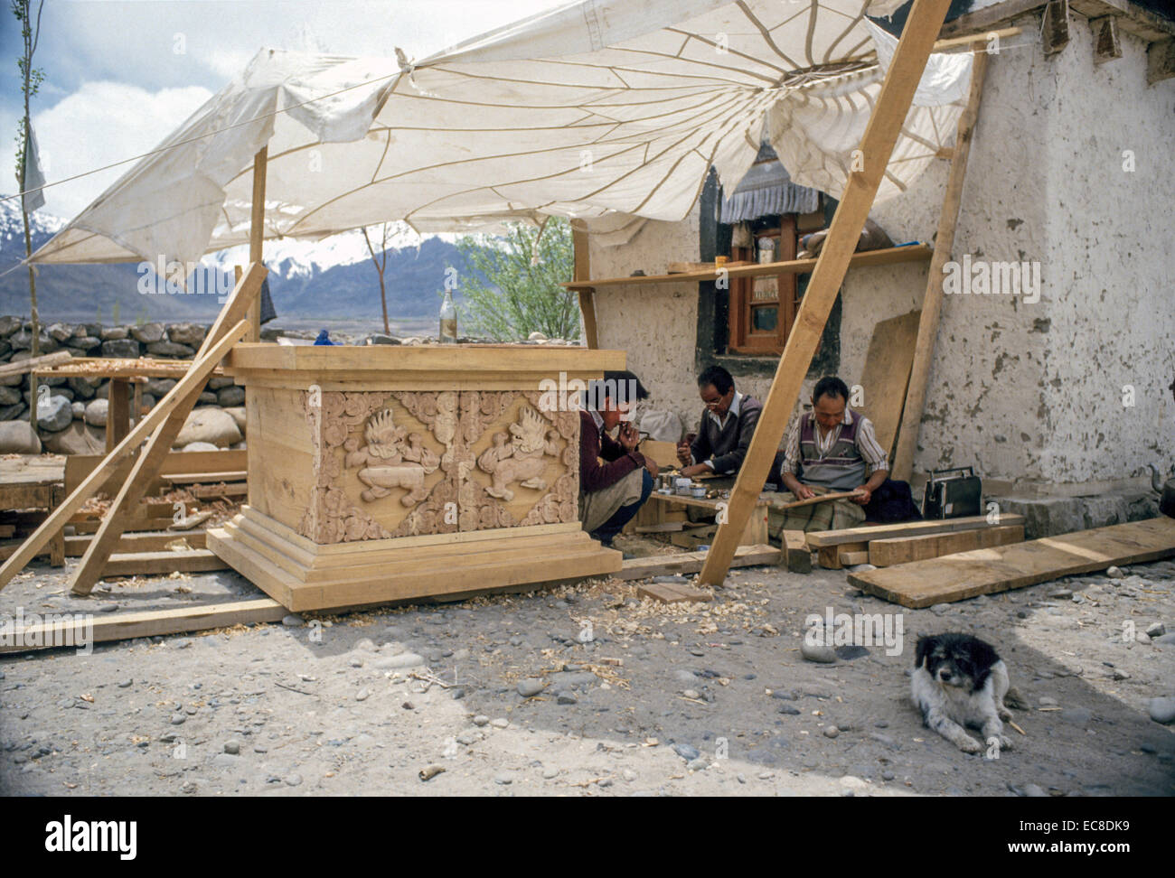 Carpenters carving a large decorative wood pedestal for a wealthy family or monastery in Leh, Ladakh. - Stock Image