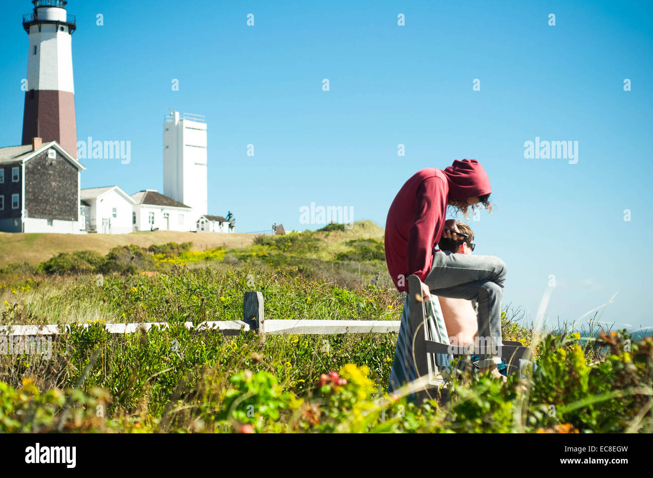 Escaping an unusually packed lineup, a local surfer checks his phone in between surf sessions at Montauk Point Lighthouse - Stock Image