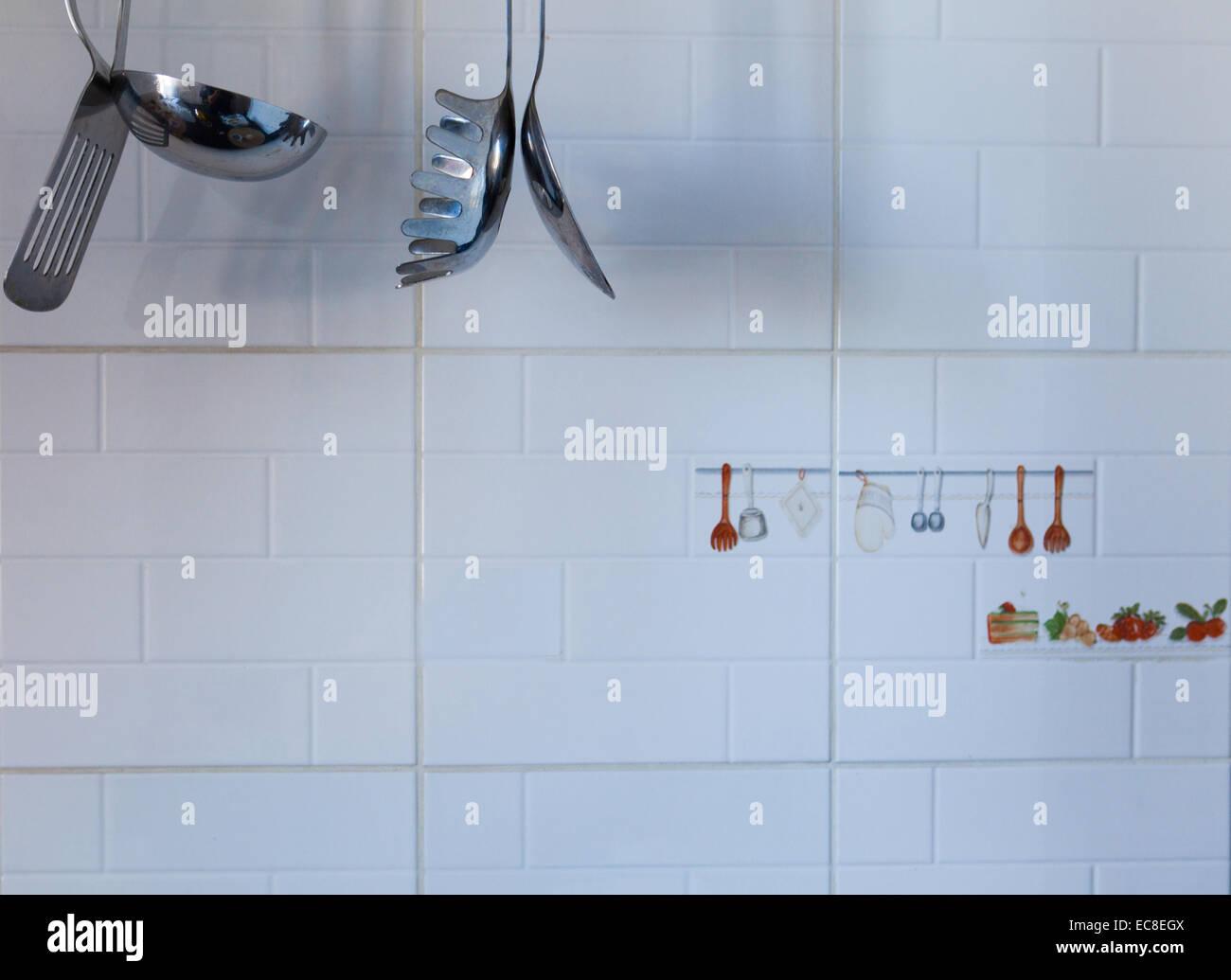 Cropped image of kitchen utensils hanging agains white metro tiles - Stock Image