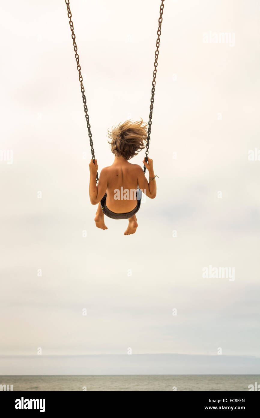 LOS ANGELES, CA – JULY 11 : Boy swinging high on a swing looking out over the ocean in Los Angeles, California on - Stock Image