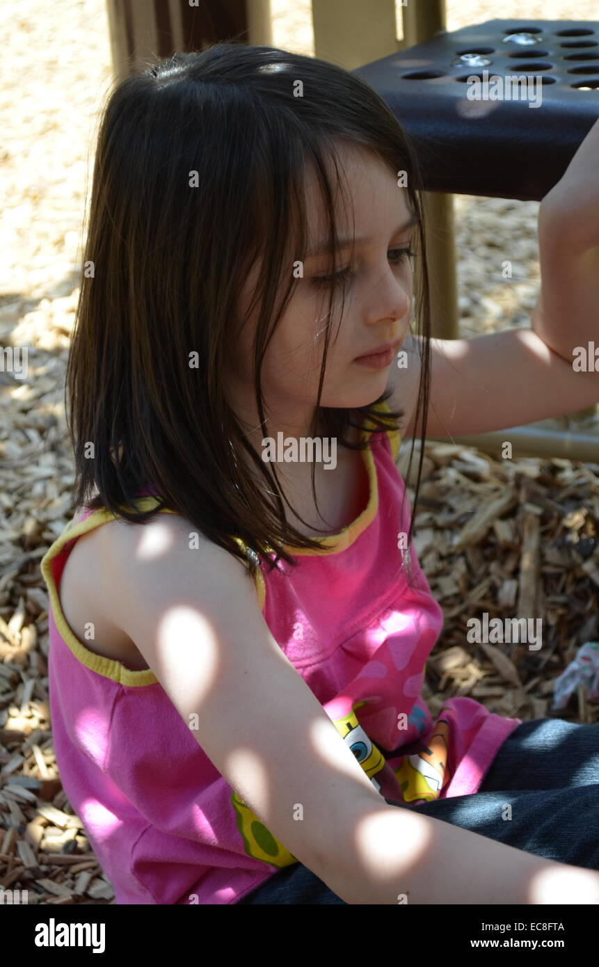 A little girl underneath the steps of play ground equipment with the sun shinning through - Stock Image
