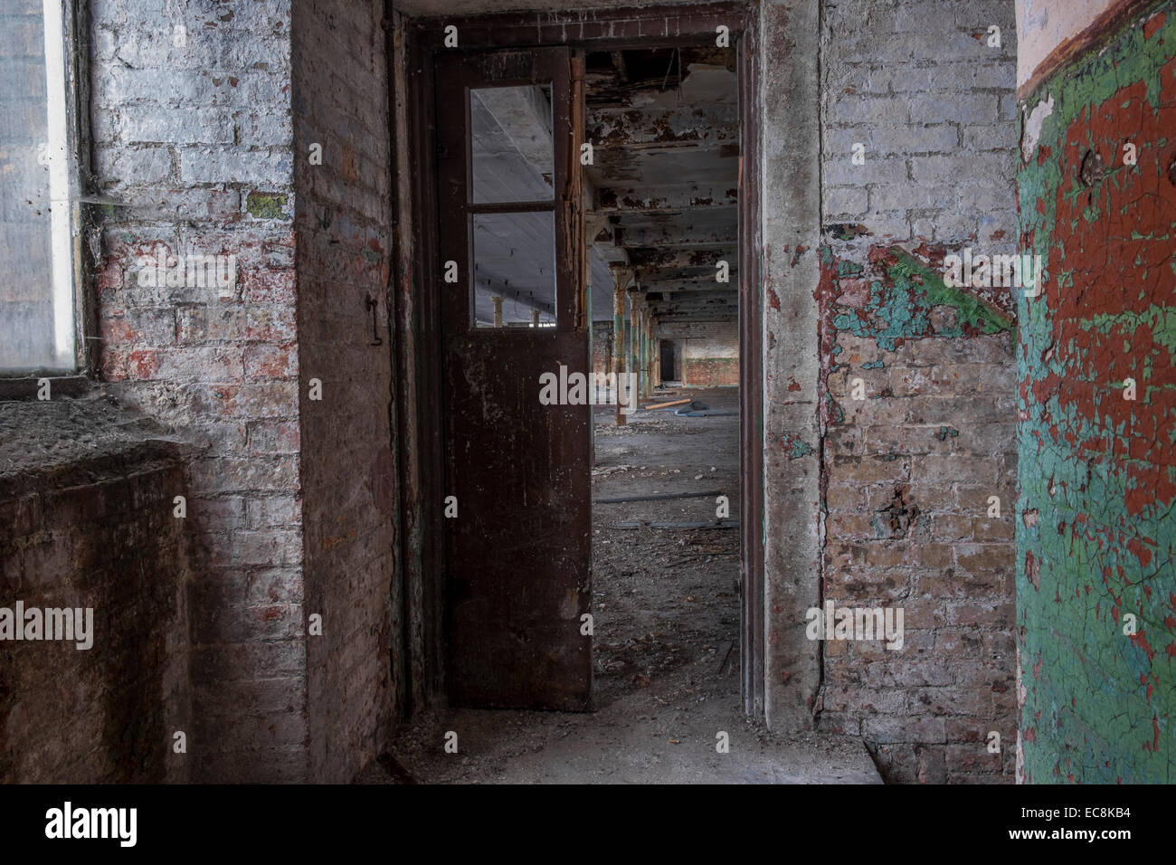 Disused old Lancashire cotton mill in a state of decay with a lot of debris on the floor area - Stock Image