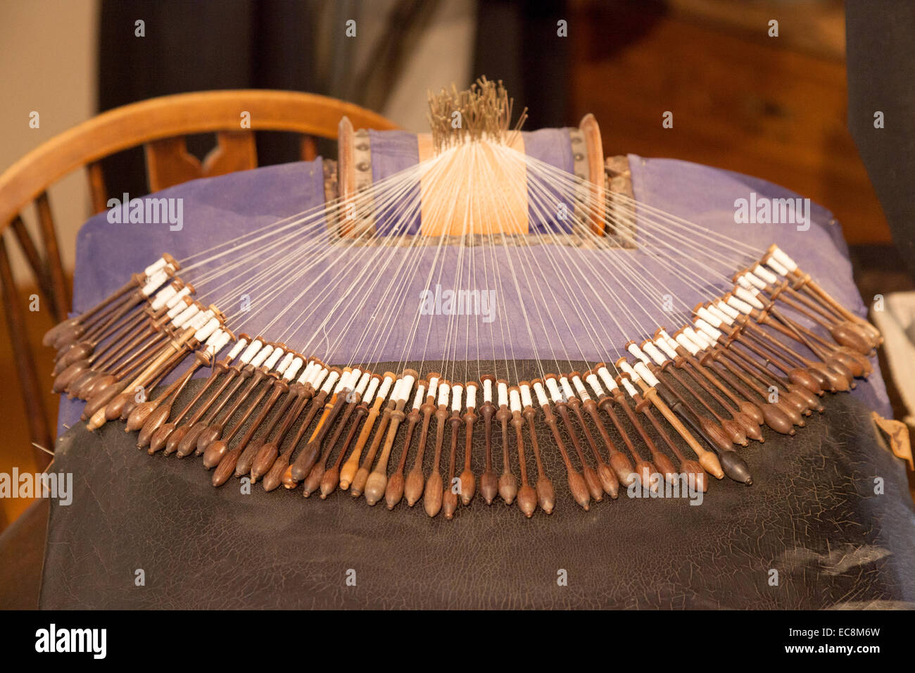 Old fashioned bobbin lace making cushion in the Museum of Folklore, Bruges, Belgium, Europe - Stock Image