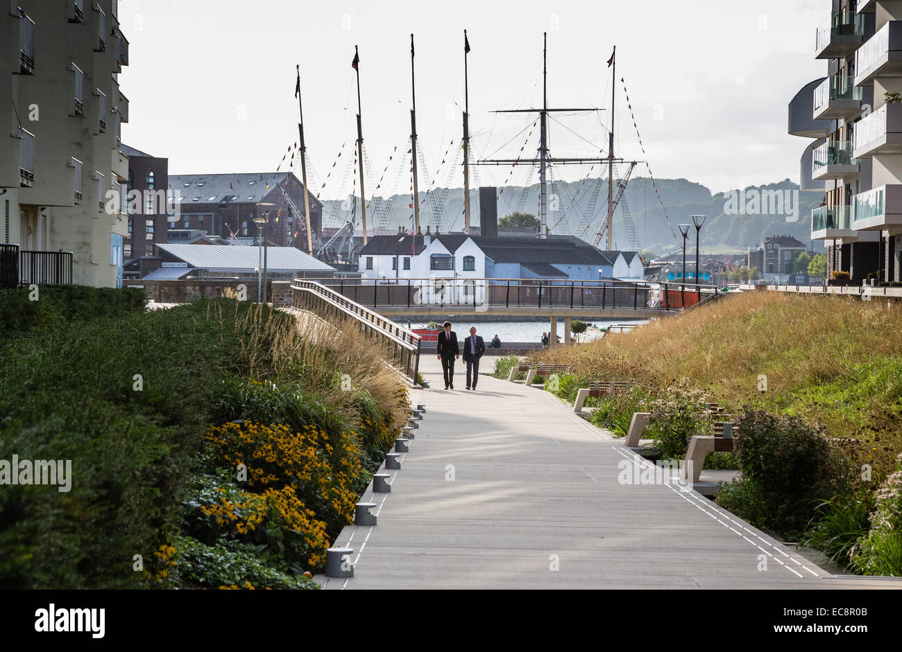Walkway past modern flats down to Bristol's floating harbour with Brunel's SS Great Britain liner in dry - Stock Image