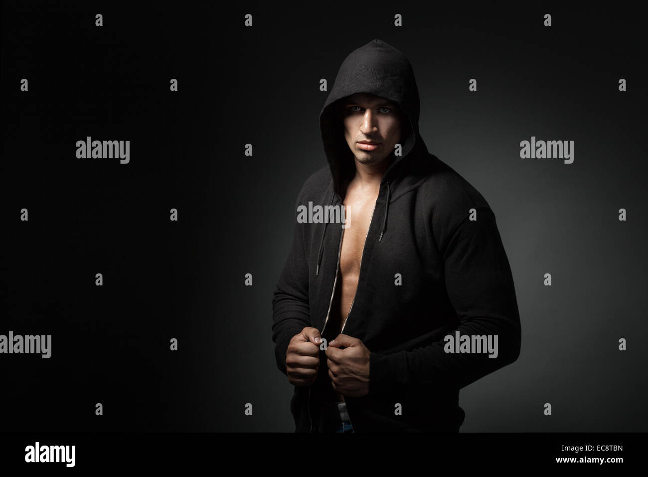 strong man wearing hoody isolated on black background with copyspace - Stock Image