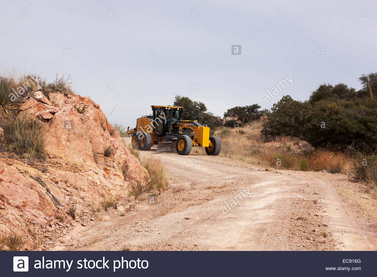 John Deere 672G Motor Grader grading forest road in southern Arizona operator visible in cab - Stock Image