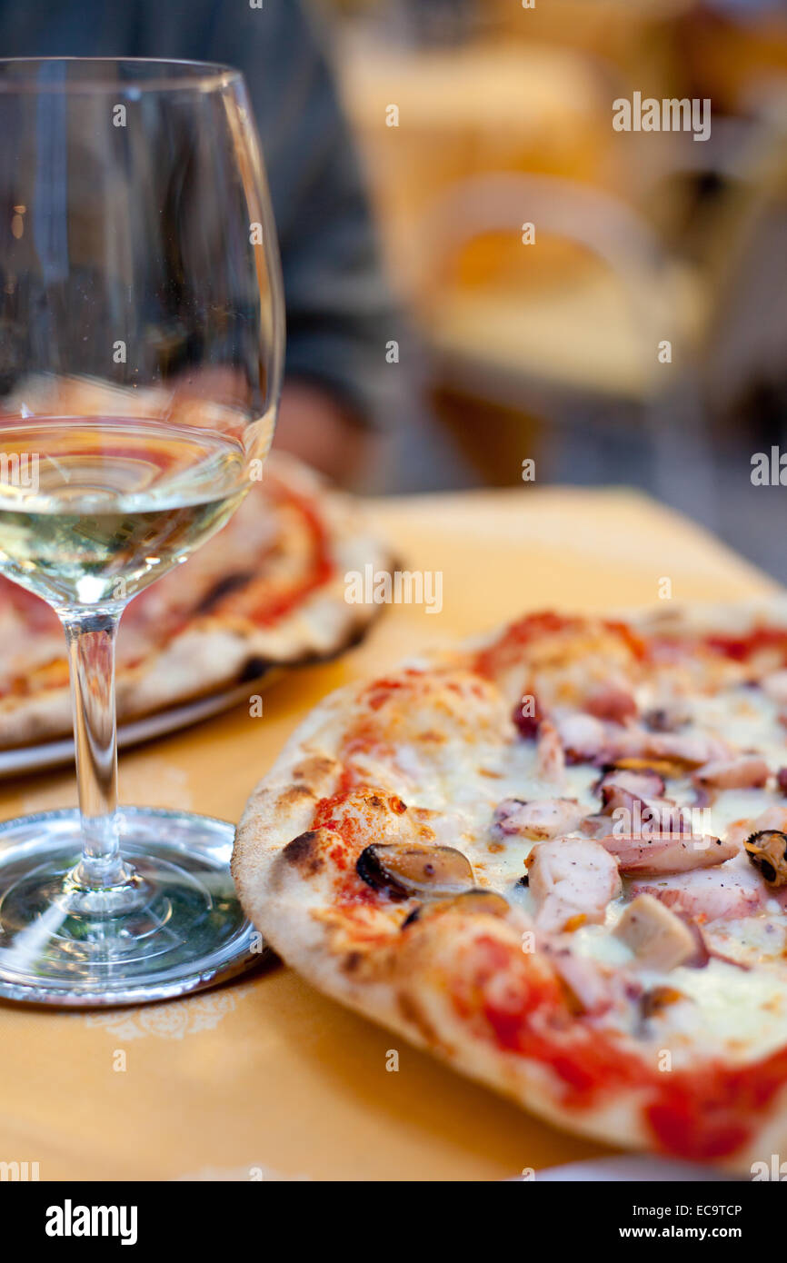 A Glass Of White Wine And Capricciosa Classical Pizza In Malcesine