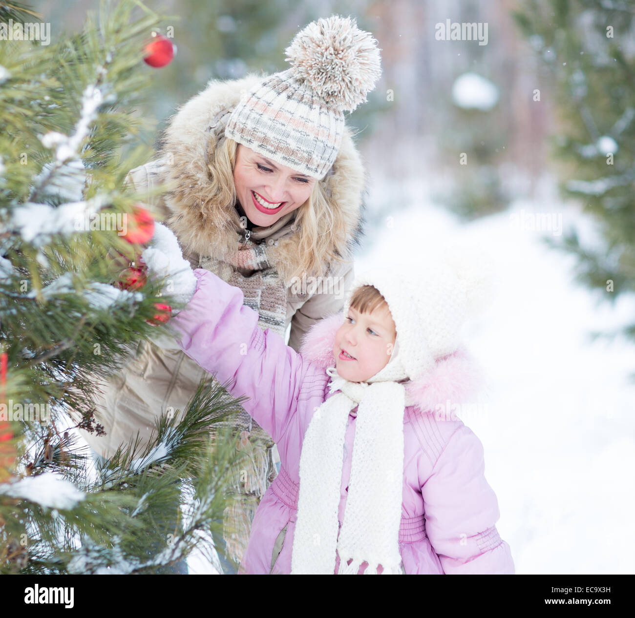 Happy family mother and child playing with christmas tree decoration outdoor - Stock Image