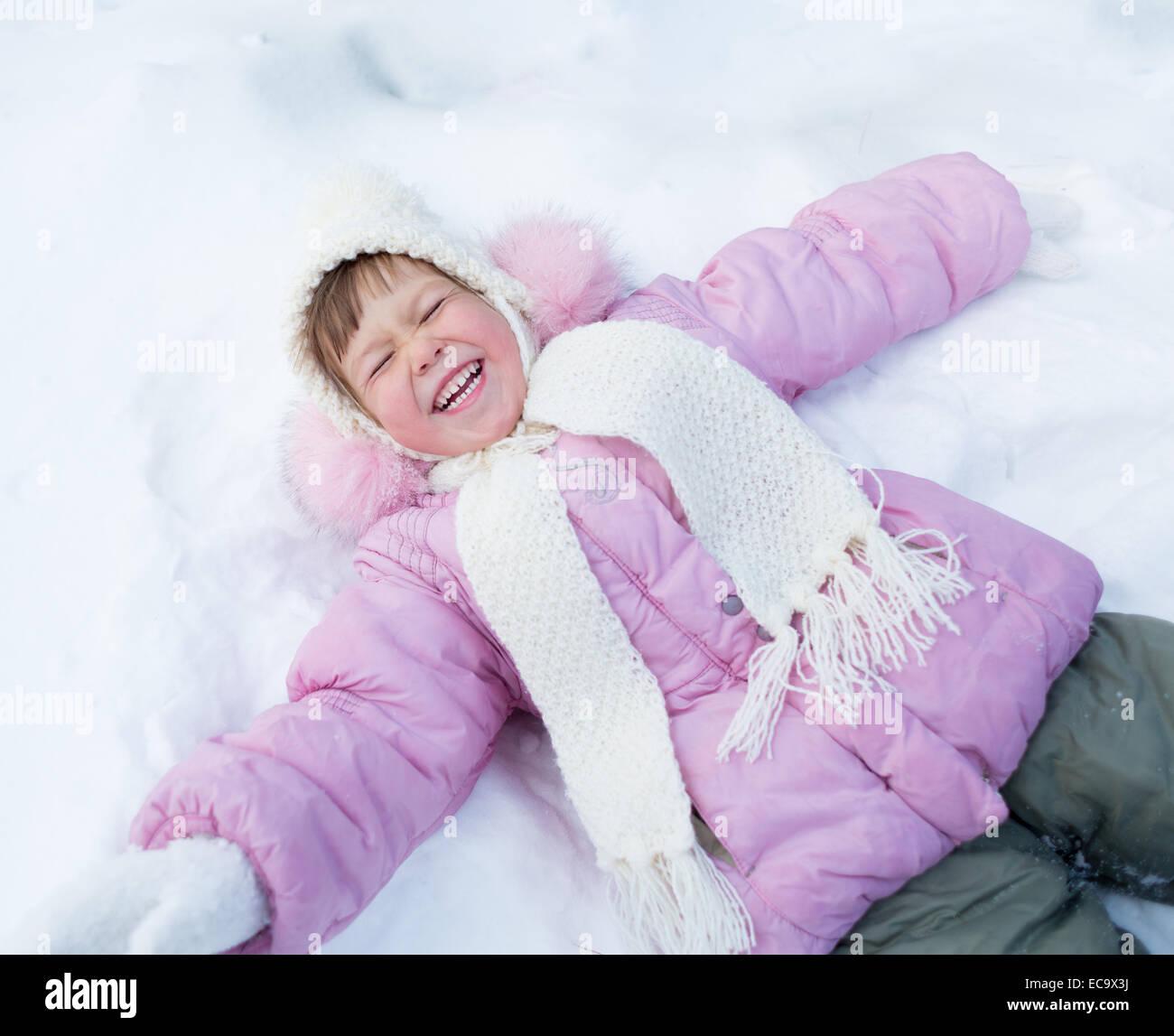 Happy kid lying on snow in winter outdoor - Stock Image