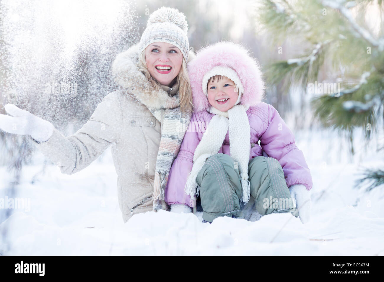 Happy family mother and daughter sitting in snow outdoor wintertime - Stock Image