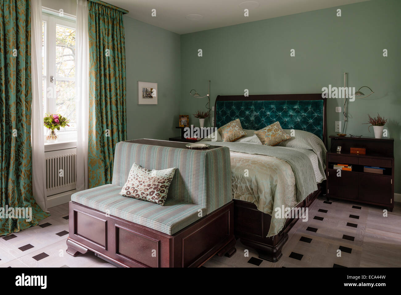 Aquamarine velvet buttoned headboard on bed in bedroom with green and gold print curtains - Stock Image