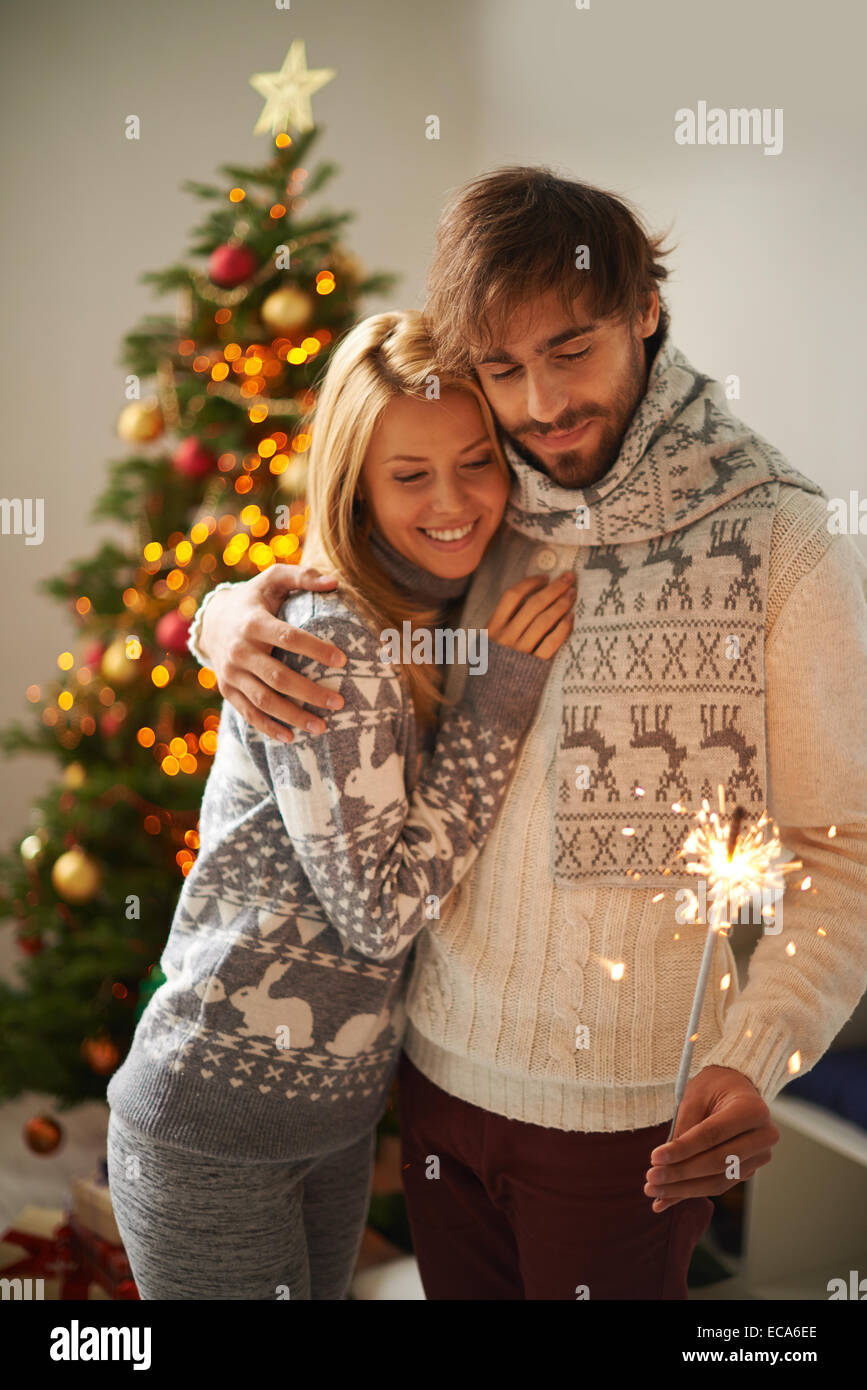 Happy young guy and girl celebrating xmas or New Year together - Stock Image