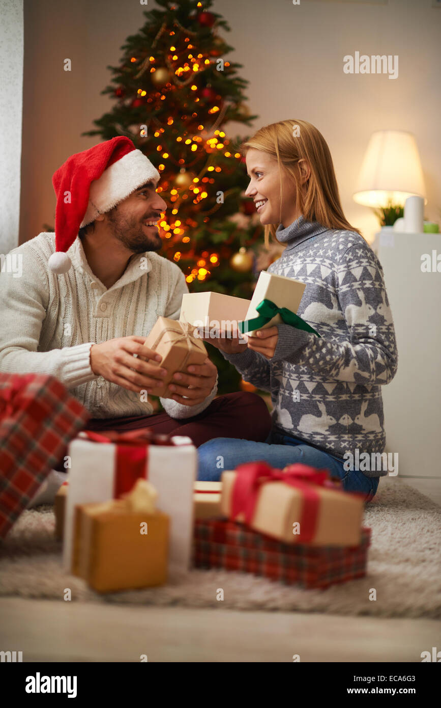 Cheerful couple opening packages with presents on Christmas night - Stock Image
