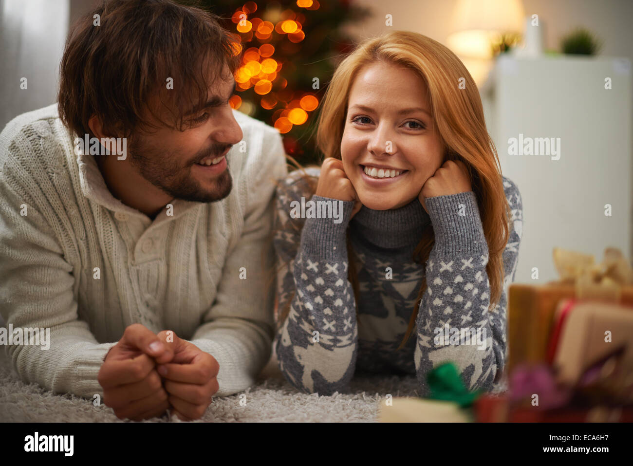 Cheerful couple lying on the floor on xmas night - Stock Image