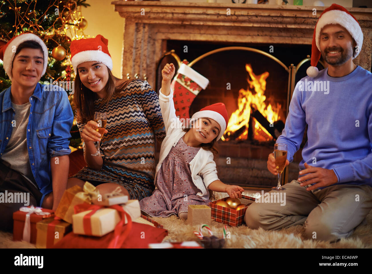 Family of four in Santa caps resting at home on Christmas evening - Stock Image