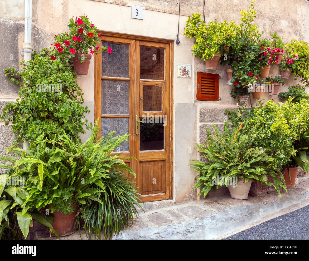 Entrance, surrounded by flowers and potted plants, Valldemossa, Majorca, Balearic Islands, Spain - Stock Image