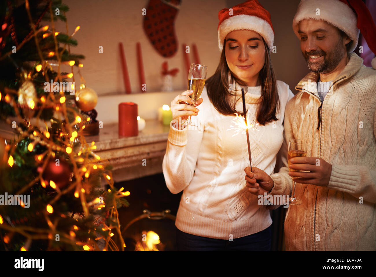 Santa man and woman with champagne looking at Bengal light on xmas night - Stock Image