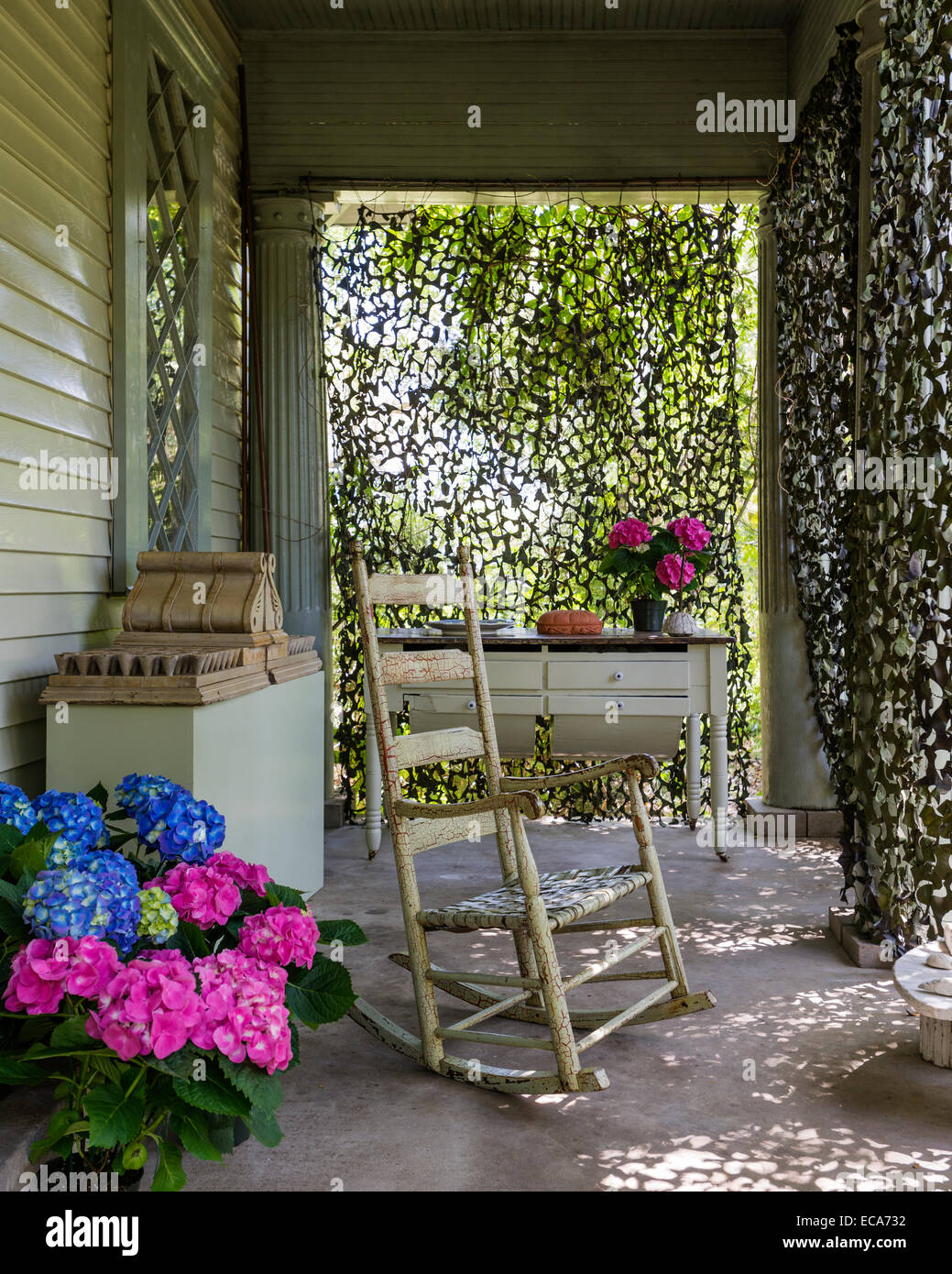 Antique texan rocking chair on porch with potted hydrangeas - Stock Image