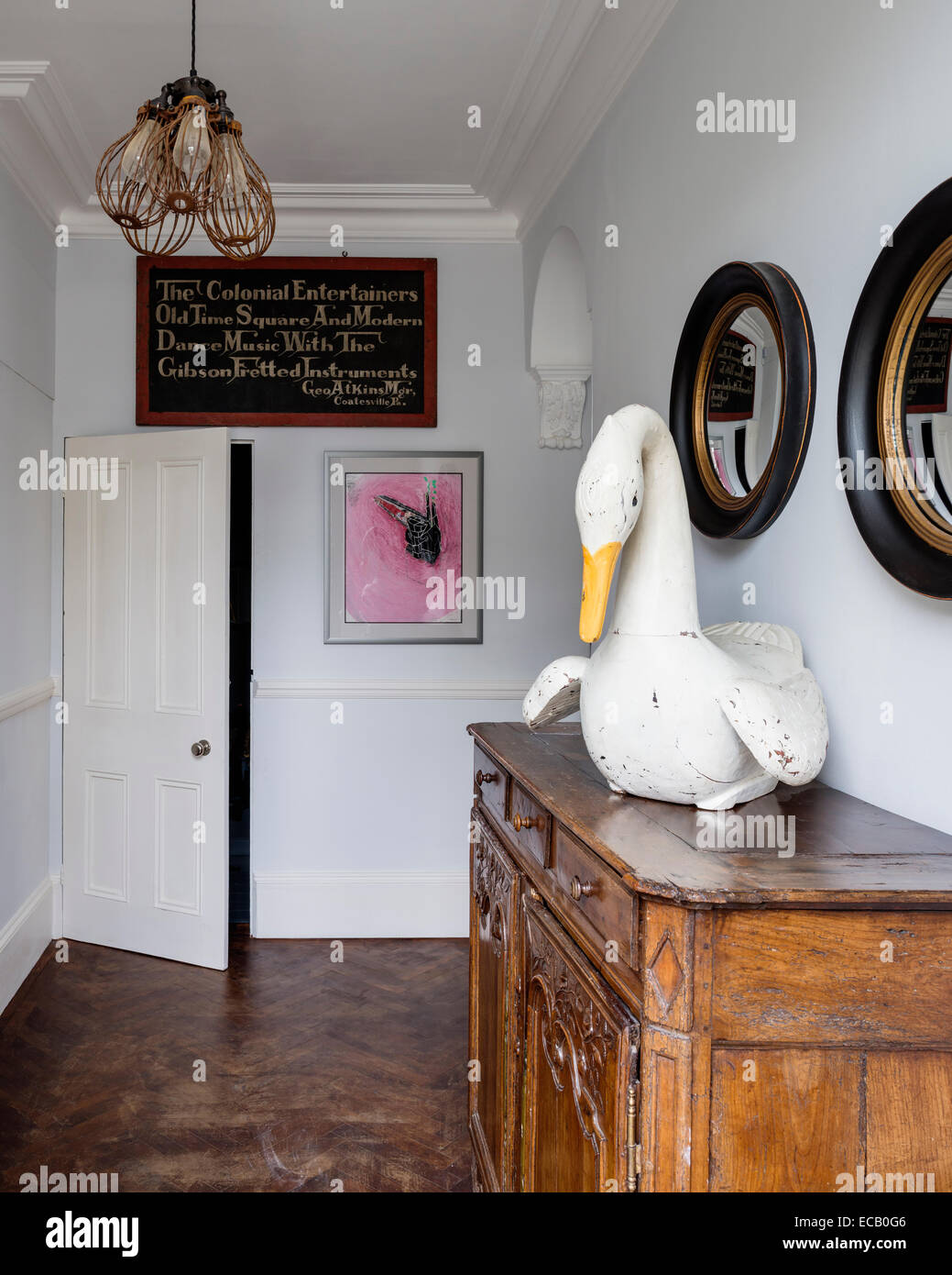 Painted wooden swan from I&JL Brown on French Provencal chest in hallway with rosewood parquet flooring. The - Stock Image