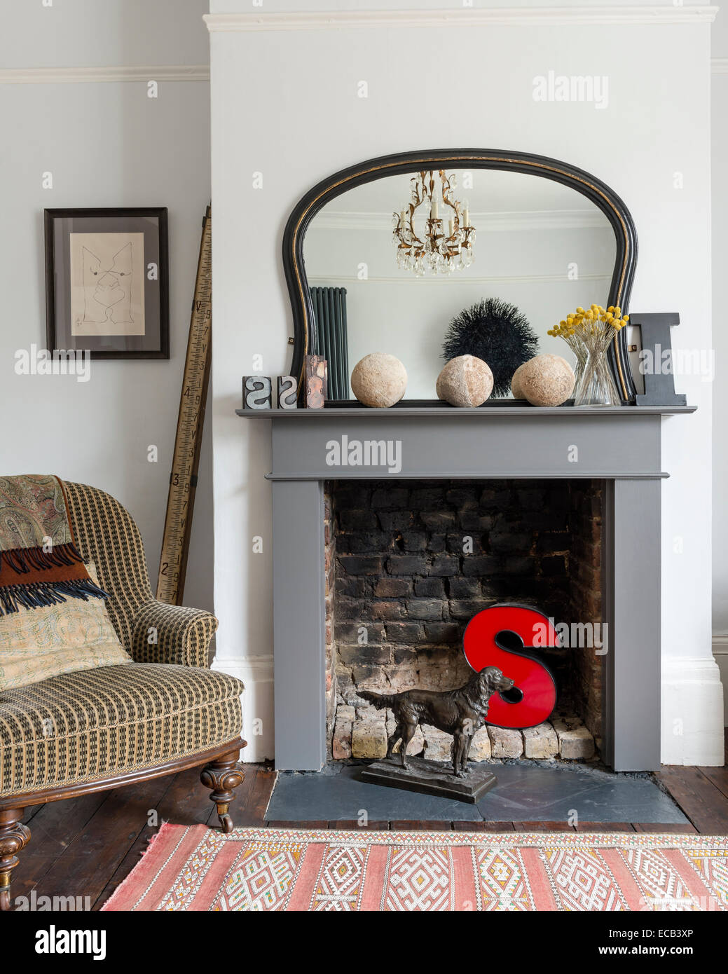 A red letter 'S' in fireplace by Victorian parlour armchair and moroccan style vintage rug - Stock Image