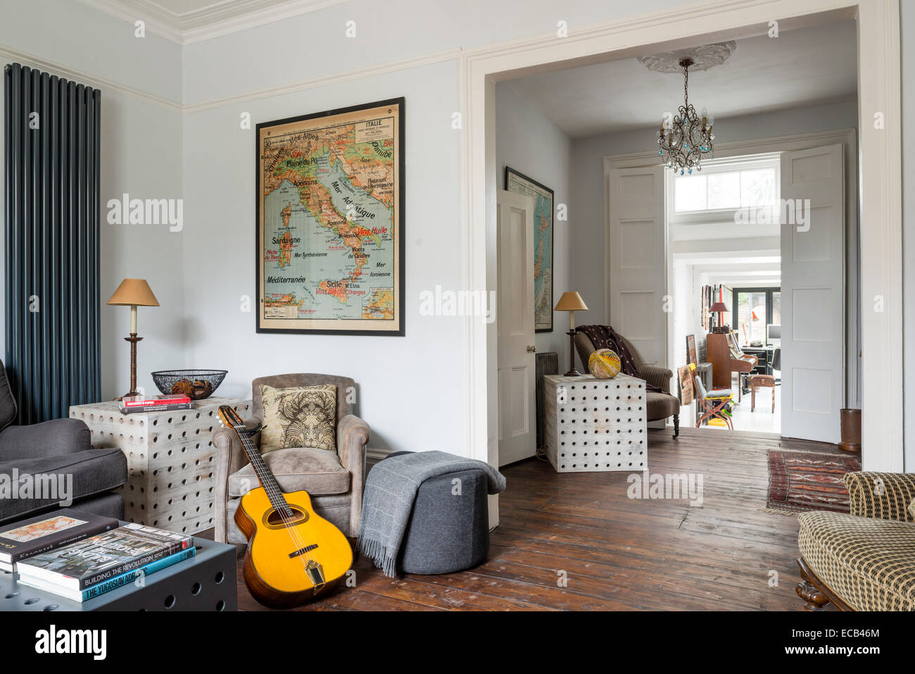 Open plan living area with large 60's school map and side tables by Selina van der Geest. - Stock Image