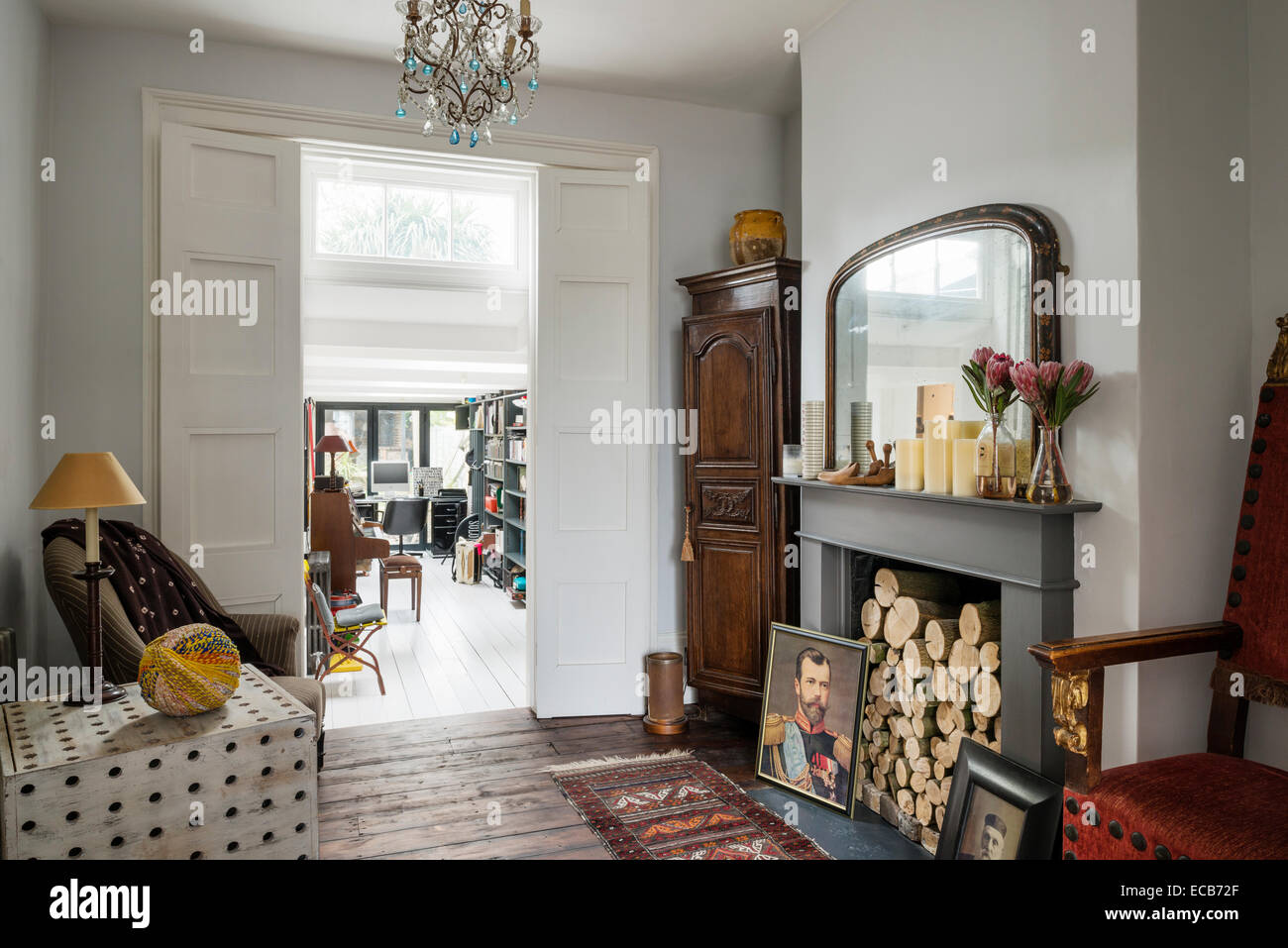 Wooden side table by Selina van der Geest in living room with wooden floors, fireplace and chandelier from Anne - Stock Image