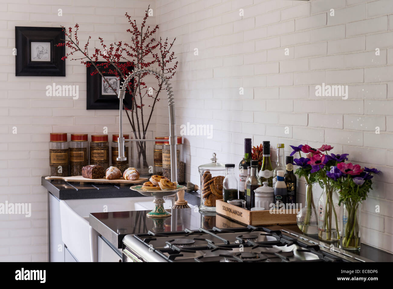 Franke tap and belfast sink in kitchen with Swedish wall tiles - Stock Image