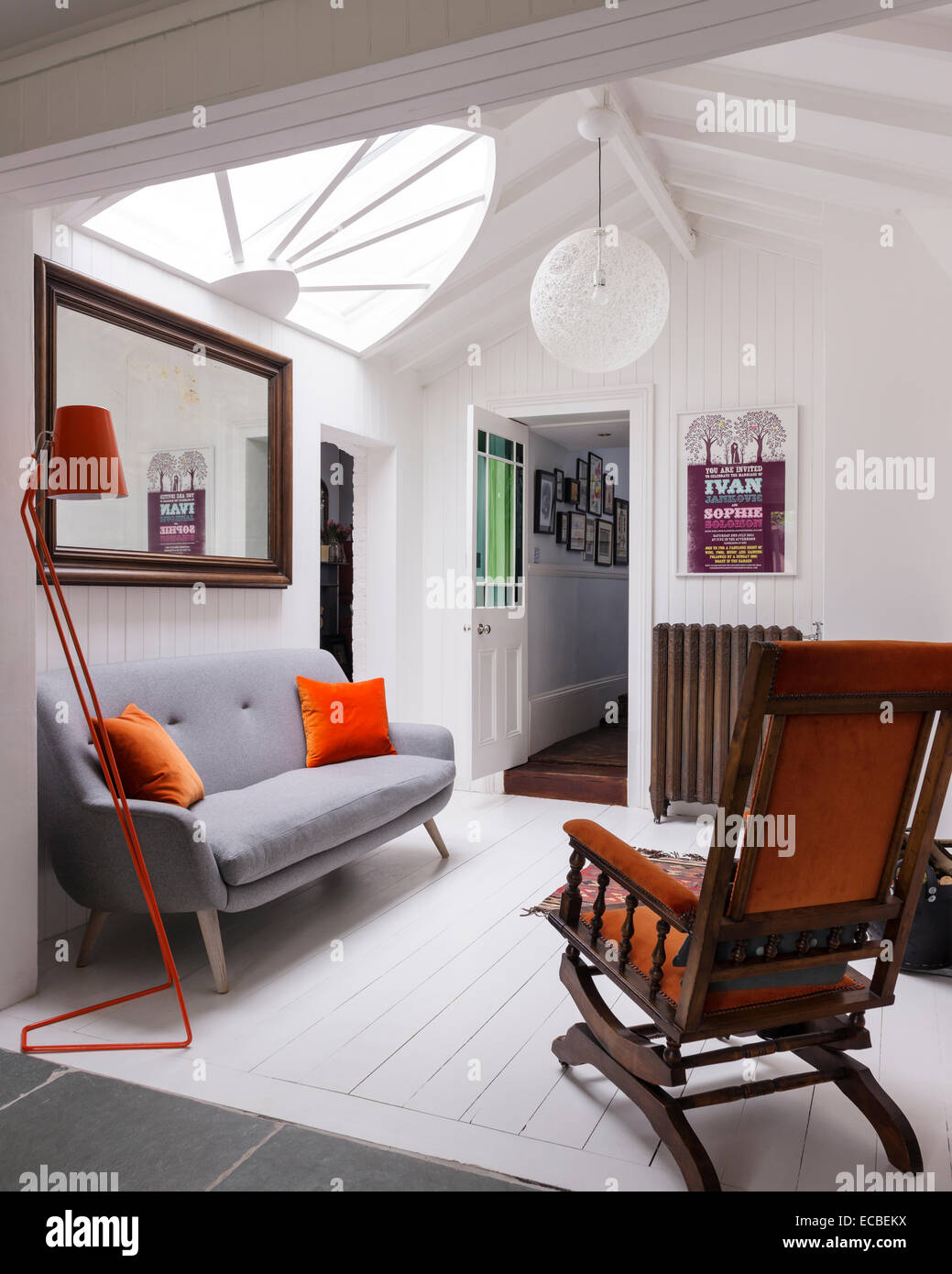 Grey felt sofa from Loaf with orange velvet cushions on landing area with orange floor lamp and large fan light Stock Photo
