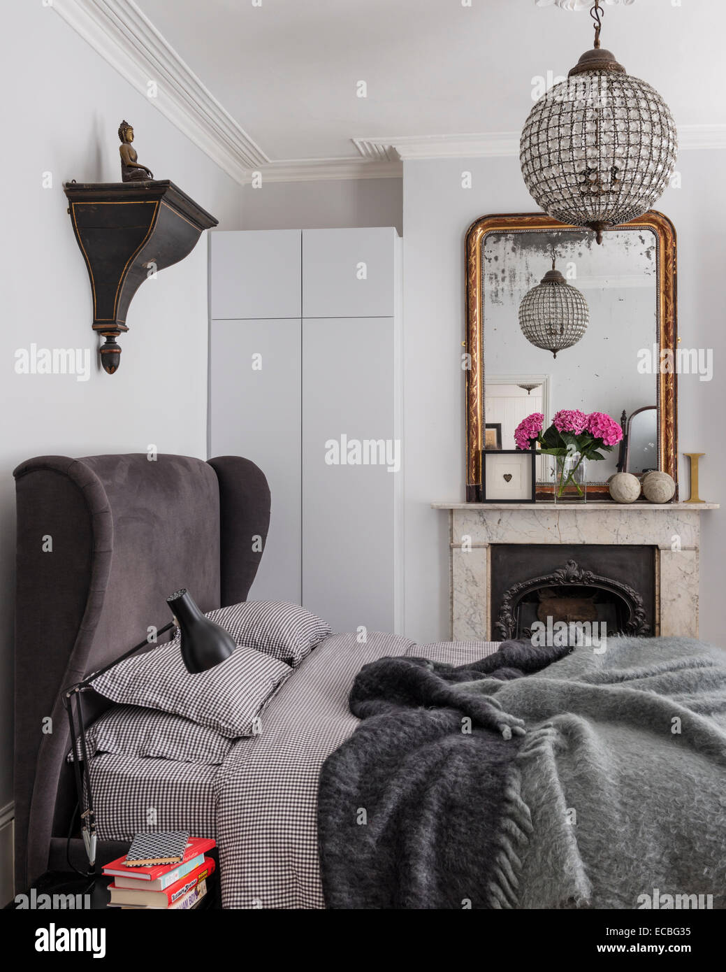 Luxury upholstered bed from sofa.com in bedroom with original fireplace, inbuilt storage and guilt framed mirror. - Stock Image