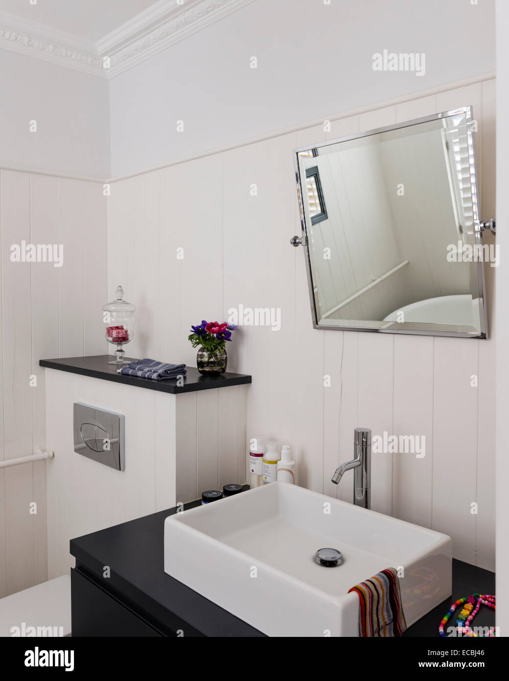 Modern sink and angled mirror in bathroom with white wood panelling - Stock Image