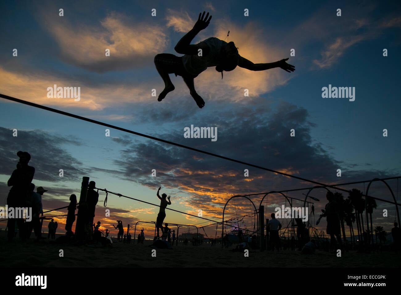 Man does backflip off a slackline. - Stock Image